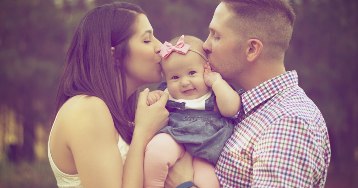 parents kiss a baby